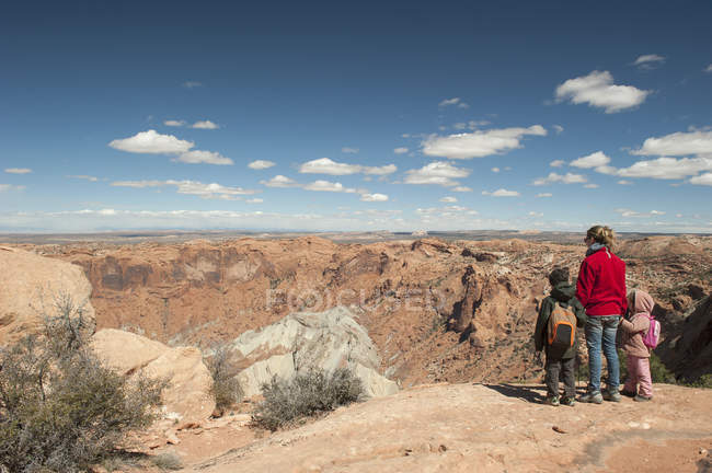 Mother and children standing at edge of canyon in Canyonlands National Park, Utah, USA — Stock Photo