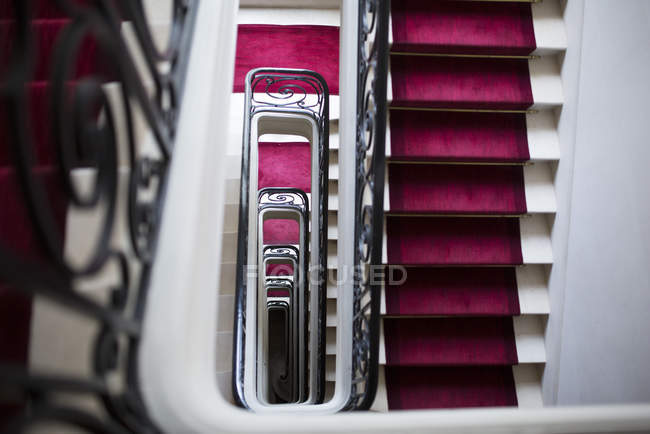 Spiral staircase with red carpet — Stock Photo