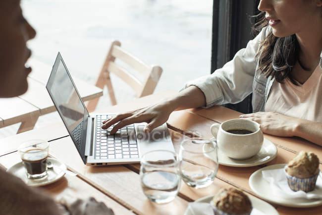 Donne che usando computer portatile nel coffee shop — Foto stock