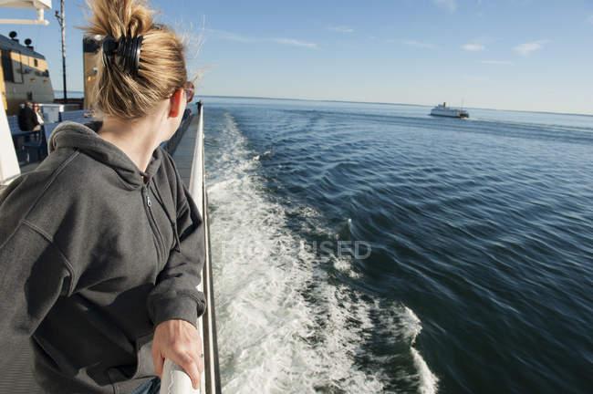 Femme debout sur le pont du bateau, regardant par-dessus l'épaule en vue — Photo de stock