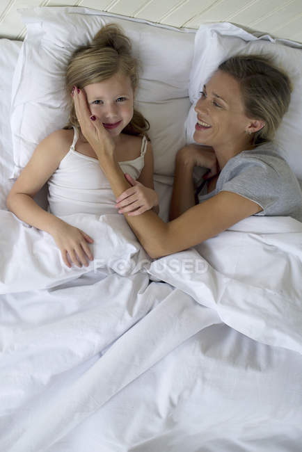 Mother and daughter lying in bed together — Stock Photo
