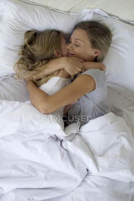 Mother and daughter in bed embracing — Stock Photo