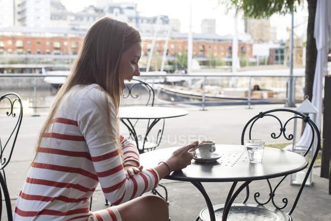Giovane donna seduta al caffè del marciapiede, ridendo di smartphone — Foto stock