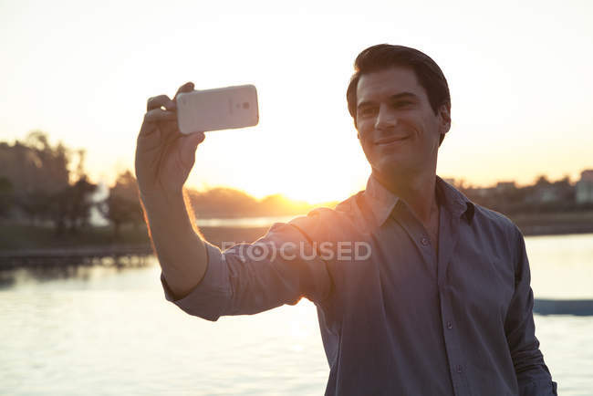 Man using smartphone to photograph himself in front of sunset — Stock Photo