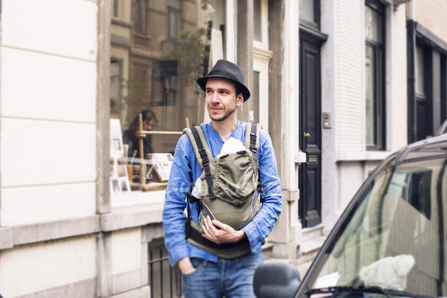 Man with baby in carrier on the move in the city — Stock Photo