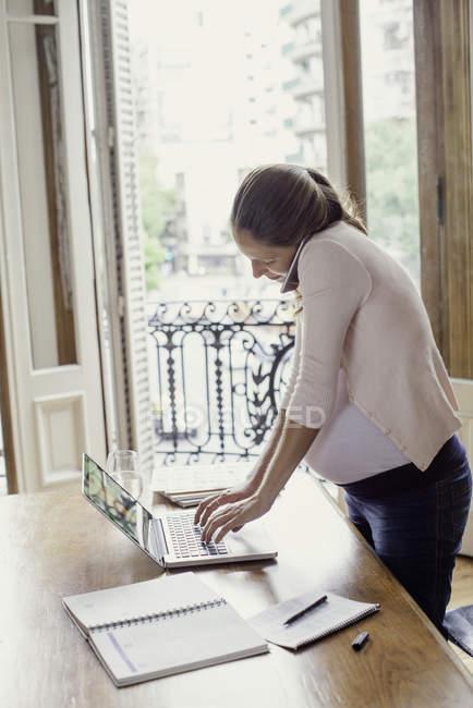 Donna incinta che lavora da casa ne sullo smartphone — Foto stock
