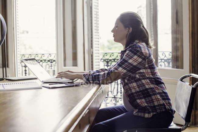 Donna utilizzando il computer portatile a casa — Foto stock