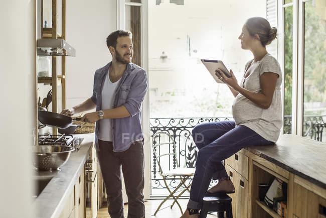 Жена смотрит на как муж готовит еду на домашней кухне — стоковое фото
