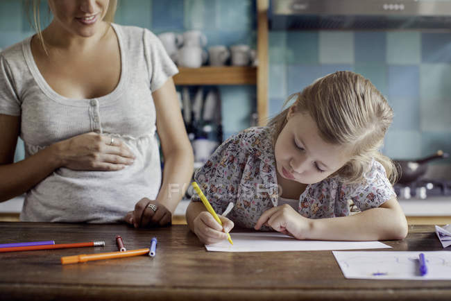Pregnant mother looking on as daughter drawing with felt tips — Stock Photo