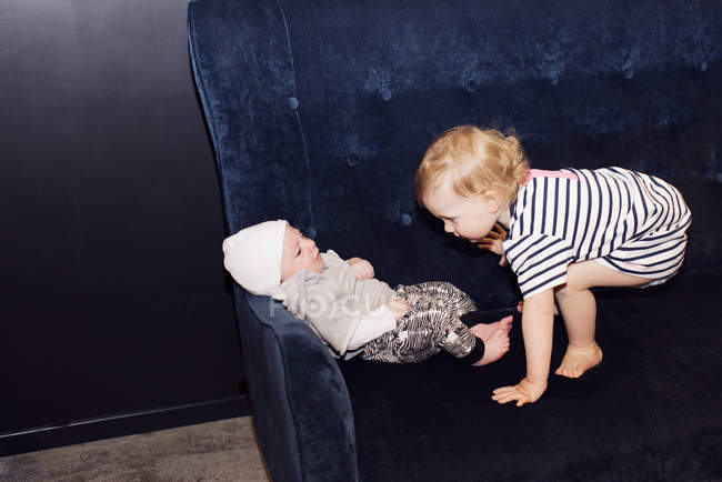 Toddler playing with infant sibling — Stock Photo