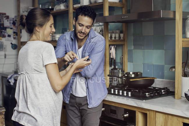 Donna che mostra il marito qualcosa sullo smartphone a casa — Foto stock