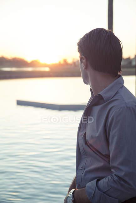 Ritratto dell'uomo che guarda il tramonto sul lago — Foto stock