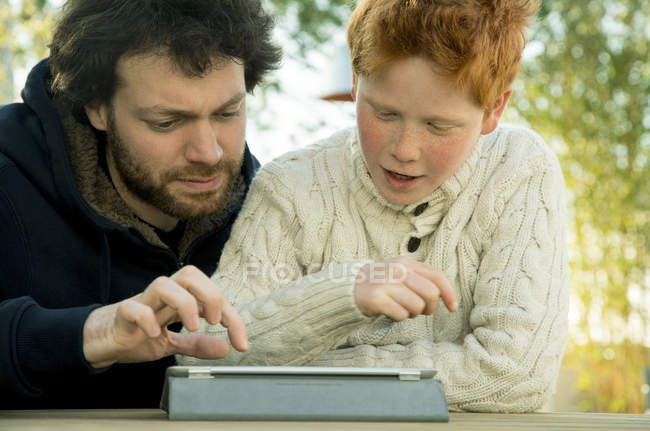 Father and son looking at digital tablet together — Stock Photo