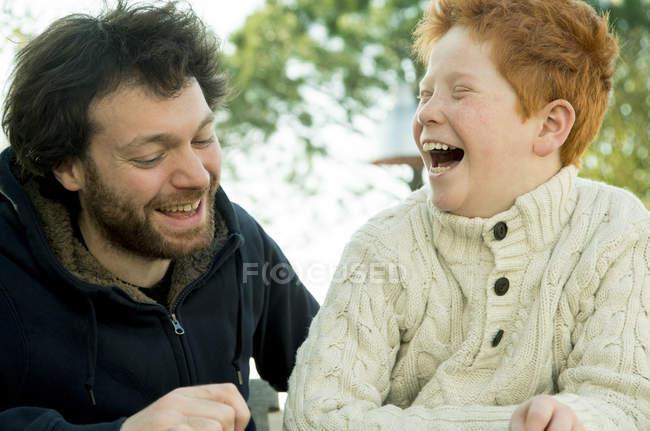 Отец и сын смеются вместе на улице — стоковое фото