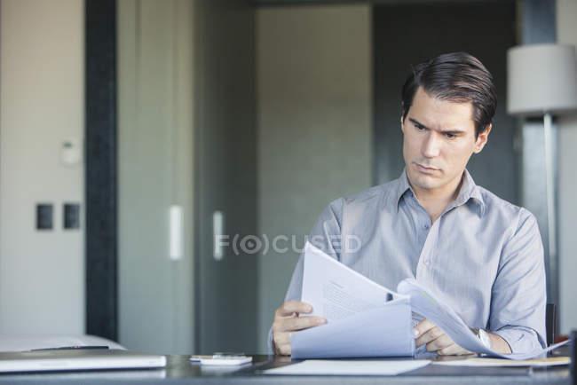 Homme lisant le document au bureau — Photo de stock
