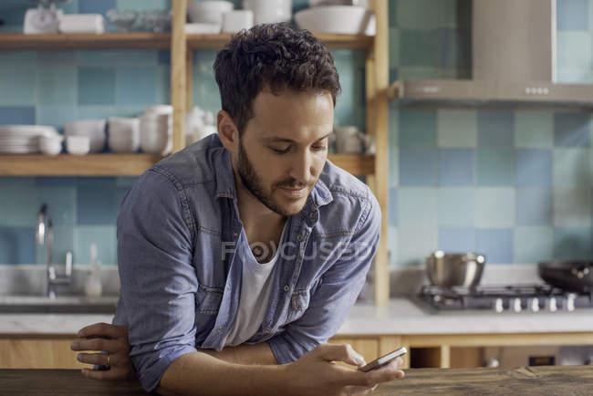 Mann zu Hause in der Küche Text-messaging — Stockfoto