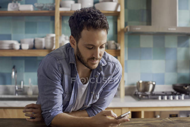 Uomo a casa in cucina messaggistica di testo — Foto stock