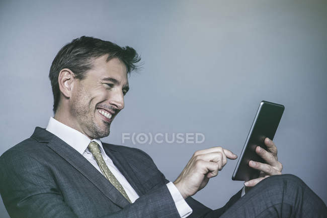 Man laughing while using digital tablet — Stock Photo