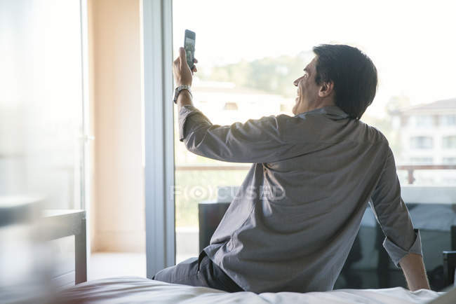Homem posando para uma selfie na cama — Fotografia de Stock