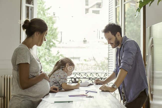 Parents regardant comme fille dessin avec feutre conseils — Photo de stock