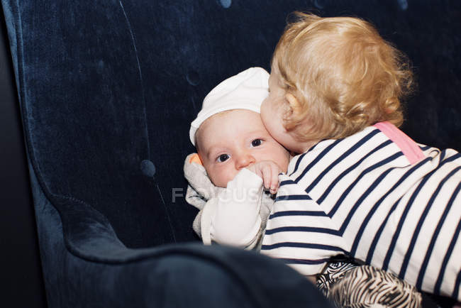 Toddler embracing infant sibling — Stock Photo