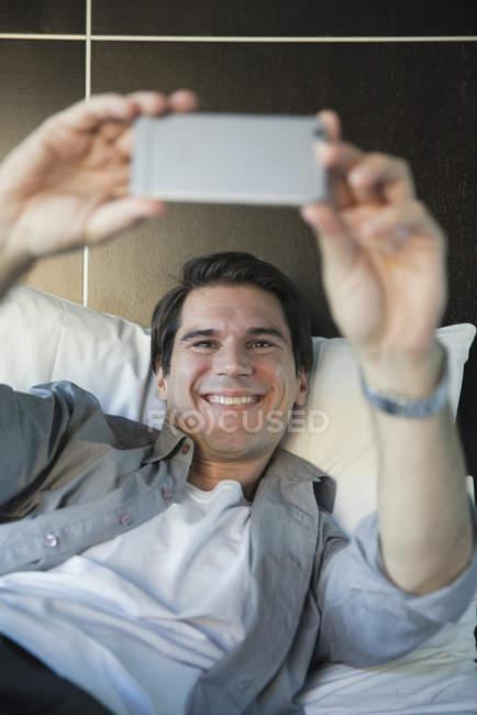 Uomo che usa lo smartphone per farsi un selfie — Foto stock