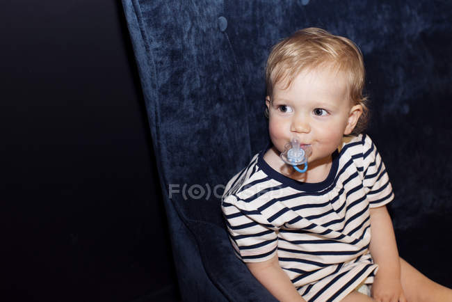 Portrait of Toddler holding pacifier in the mouth sitting on the couch — Stock Photo