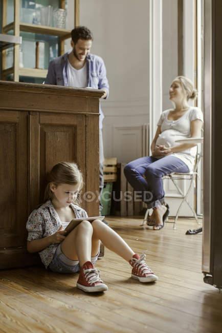 Chica sentada sola jugando videojuego mientras los padres charlan - foto de stock