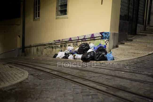 Basura en el lado de la calle empedrada - foto de stock