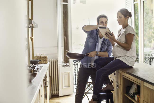 Пара ссылок на цифровой планшет во время приготовления еды — стоковое фото
