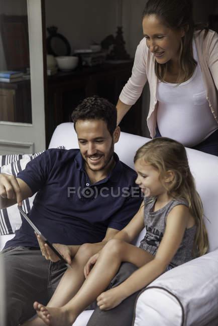 Famiglia con tavoletta digitale insieme a casa — Foto stock