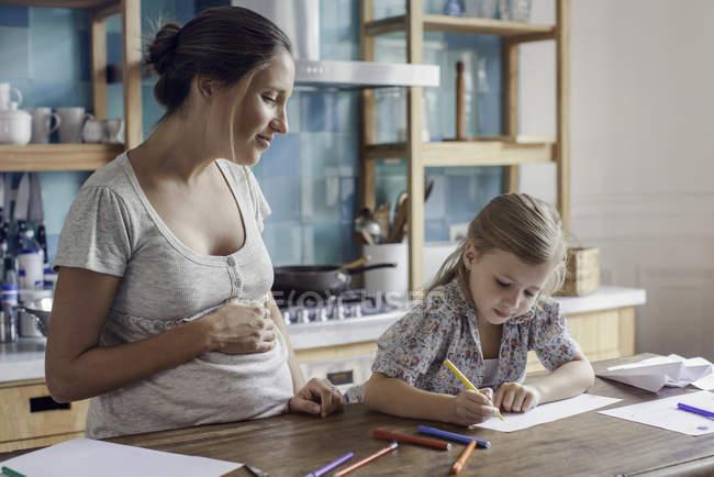 Mère enceinte regardant sa fille dessiner avec des stylos en feutre sur la cuisine — Photo de stock
