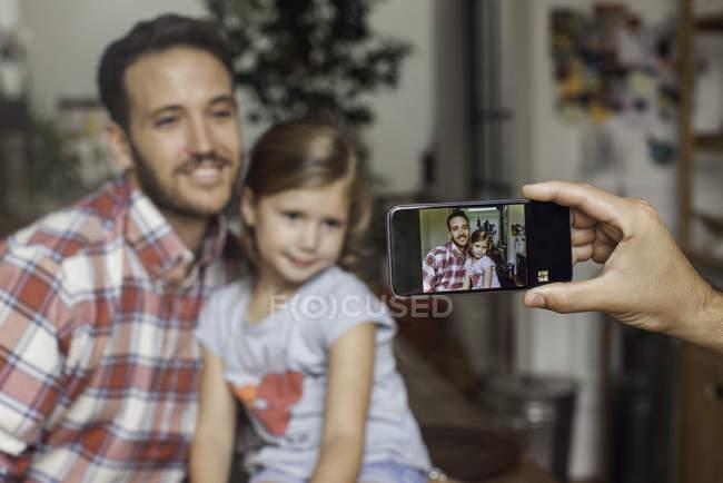 Женщина рука фотографа отца и дочери со смартфоном — стоковое фото