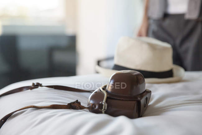 Camera and straw hat on bed in hotel room — Stock Photo