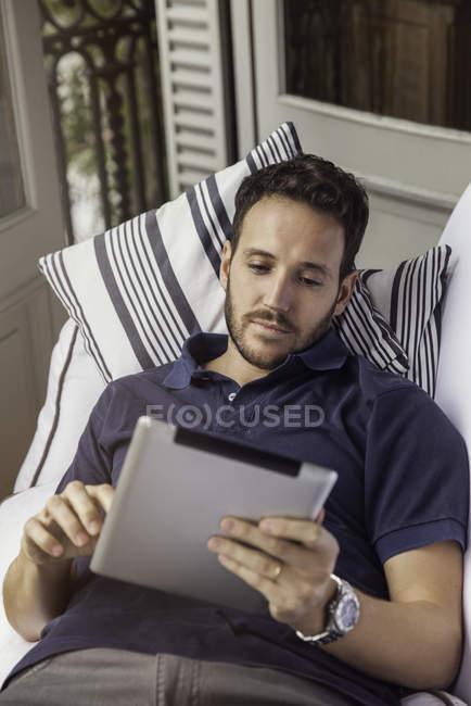 Человек с цифровой планшет лежал на кровати — стоковое фото