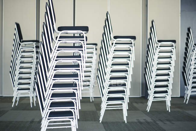 Stacks of chairs in empty office room — Stock Photo