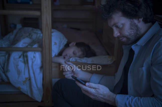 Father checking smartphone while comforting sick daughter — Stock Photo