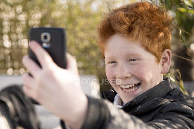 Boy using smartphone to take a selfie — Stock Photo