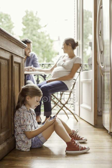 Ragazza assorto nel video gioco mentre i genitori chiacchierano nella priorità bassa — Foto stock
