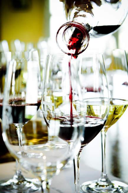 Крупним планом розливом червоного вина в той окуляри — стокове фото