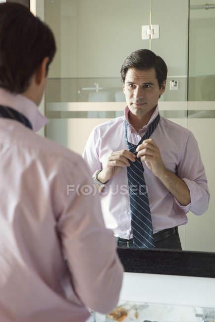 Человек, регулируя галстук в зеркало в ванной — стоковое фото