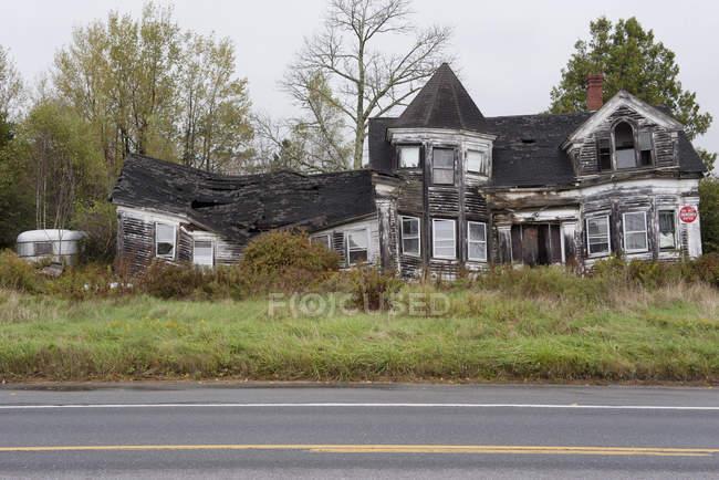 Фасад покинуті спалив будинок біля дороги — стокове фото