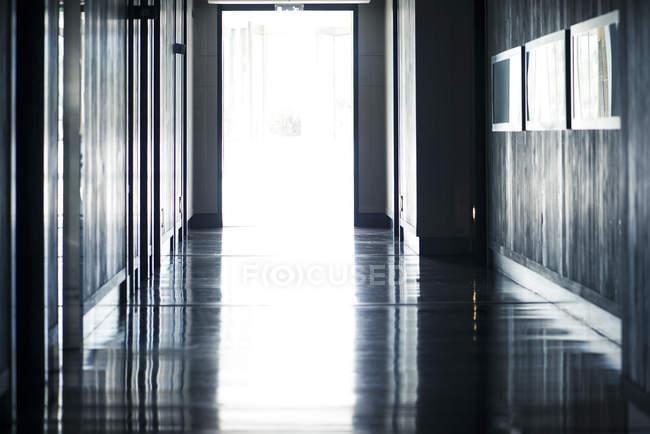 Puertas abiertas en el final del pasillo vacío - foto de stock