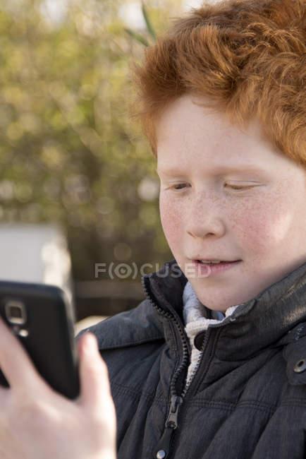 Boy using smartphone outdoors — Stock Photo