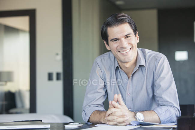 Portrait of smiling Businessman sitting at desk — Stock Photo