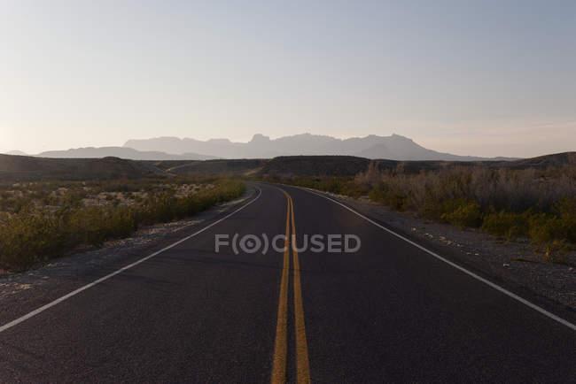 Rodovia através de uma paisagem árida de dia — Fotografia de Stock
