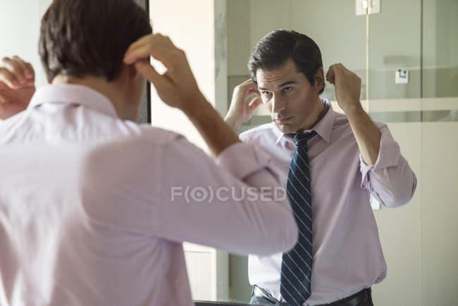 Мужчина чинит волосы в зеркале в ванной — стоковое фото