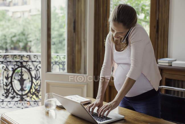 Беременная женщина работает из дома разговаривает по смартфону — стоковое фото