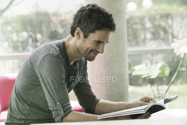 Uomo che osserva attraverso la rivista durante l'attesa in sala d'attesa — Foto stock