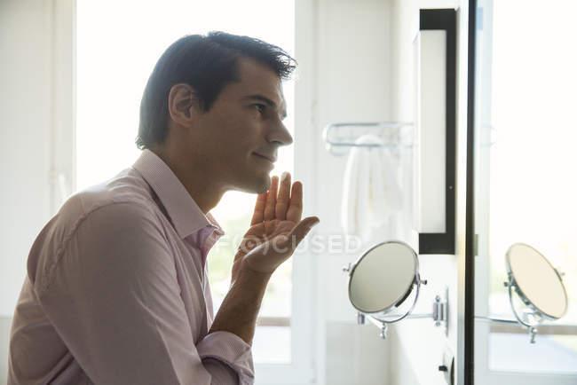 Mann schaut in Spiegel und trägt Feuchtigkeitscreme auf Gesicht auf — Stockfoto